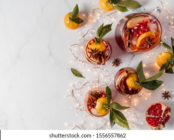 Winter sangria on white marble background. Jugful of sangria and glasses with with orange slice, pomegranate and spices. Copy space for text or design. Horizontal. Top view or flat lay.