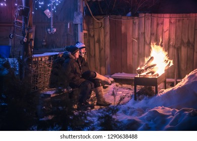 Winter scene children boys get warm at fire in night snowy countryside