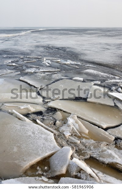 Winter scene at a frozen lake with ice-pack and other ice formations