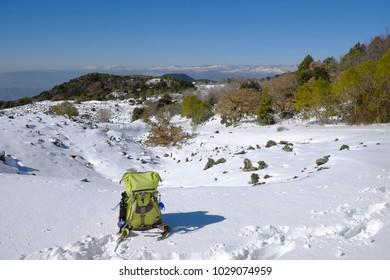 winter scene with green backpack in Etna Park, Sicily
