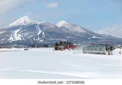 Winter scene of a local train traveling on  Ban'etsu West Line Railway from Inawashiro to Kawageta through country fields covered by snow and Mount Bandai dominating the background in Fukushima, Japan