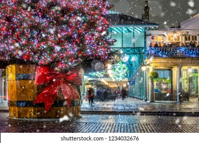 Winter scene in London Covent Garden with a Christmas tree and snowfall, UK