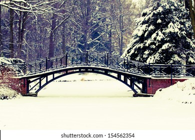 Winter scene - Old bridge in winter snowy park