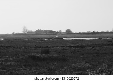 Winter scene of salt marsh and water ways with grass and boats on a cold windy and over cast day. A run down charm with boats slowly rusting and nature taking over
