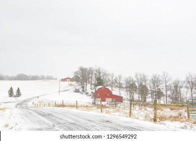 Winter scene of a snow-covered road leading past a farm with red barns in rural Appalachia during a snow storm with negative space above for copy.