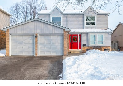 A Winter Scene of a Suburban Detached House with Grey Siding and Red Door Decorated with a Christmas Wreath