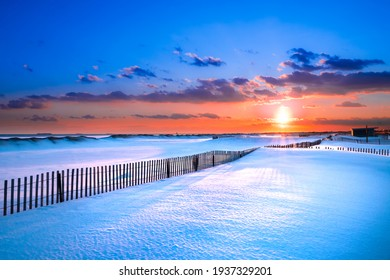 Winter scene under color sky at sunset on snow covered beach. Jones Beach State Park., Long Island NY