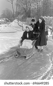 Winter scene of woman and man pushing sleigh