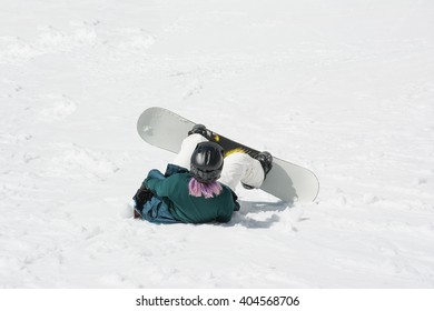 Winter scene of  the young woman skier falling down on mountain slope