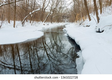 winter scenery with fresh fallen snow along creek in minnehaha parkway of minneapolis minnesota