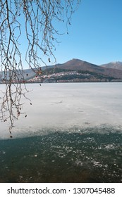 Winter scenery with frozen lake and some tree branches as frame at the lake Orestiada in Kastoria,Greece