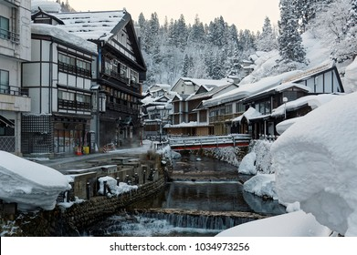 Winter scenery of Ginzan Onsen, a famous Japanese hot spring town in Obanazawa, Yamagata, Japan, with bridges over a stream flanked by historical wooden buildings after heavy snowfalls in the morning
