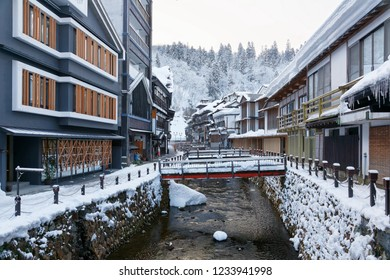 Winter scenery of Ginzan Onsen, a popular hot spring town in Obanazawa, Yamagata, Japan, with bridges over a stream flanked by Japanese Ryokan and historical wooden buildings after heavy snowfalls