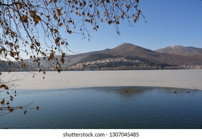 Winter scenery with half frozen lake and  tree branches as frame at the lake Orestiada in Kastoria,Greece