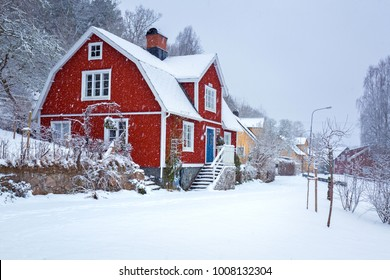 Winter scenery with red wooden house in Sweden