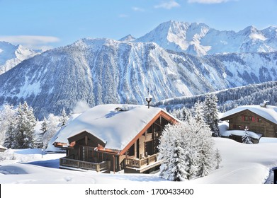Winter scenery with snowy mountains and beautiful wooden chalet in French Alps, Courchevel