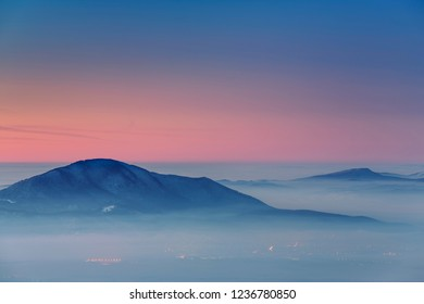 Winter scenery with sunset over the misty valleys of the Carpathians mountains, Transylvania region, Romania.