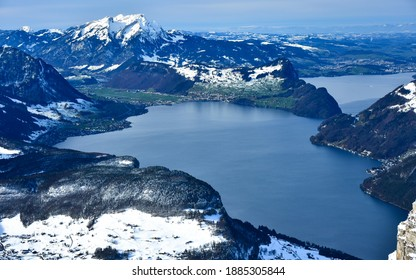 Winter scenery in Swiss Alps. Top view of a lake from the highest point in Stoos Ski Resort. The snowed, rocky, sharp, steep peaks surround the blue waters.