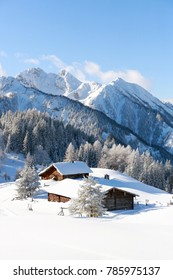 Winter scenery with a traditional alpine hut covered with a snow