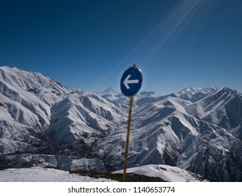 Winter scenery with traffic sign pointing at Damavand peak