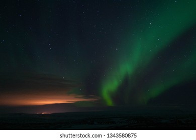 Winter scenic landscape night view of  Aurora Borealis/Northern lights dancing on the clear sky full of stars above lake Myvatn, north Iceland Beautiful winter wonderland/fairytale background scene.