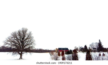 Winter scenic wide red barn country farm in the Winter with snow and barren trees