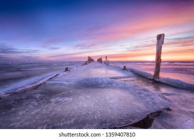 Winter seascape of wood breakwaters on frozen Baltic sea
