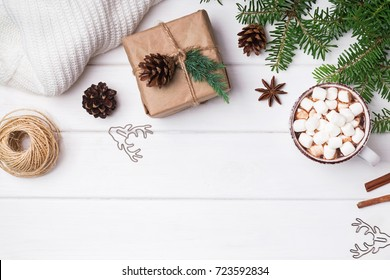Winter season accessories: hot cocoa, fir branches and knitted sweater on the white background