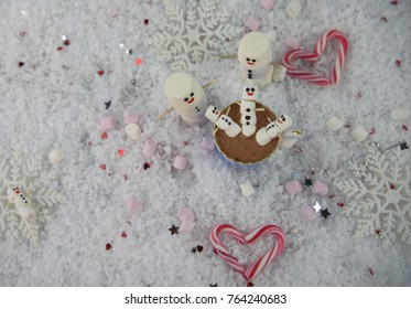 winter season food and drink photography image of hot chocolate cup filled with mini marshmallows with iced on smile and placed on snow with candy cane hearts and snowflakes