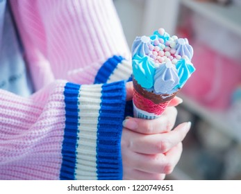winter season and holiday event concept from beautiful woman finger and hand in pink warm suit hold and show colorful icecream in living room decorate with christmas and new year item background