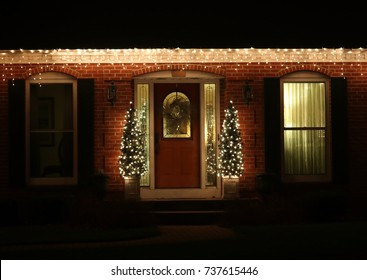 Winter season house outdoors decoration. Night scene with porch and front yard of the house decorated by glowing in the dark garlands. Christmas and New Year holiday background.