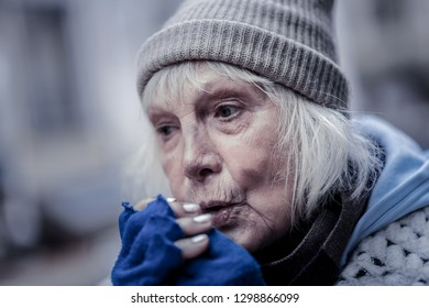 Winter season. Portrait of a sad senior woman blowing at her hands while feeling cold