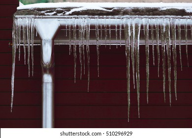 Winter season scene. Icicles on the roof. cold weather concept. Frozen icy down pipe waterspout on brown wooden background.