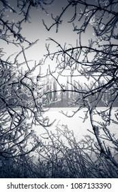 Winter season in Slovakia. Landscape framed by frozen branches.