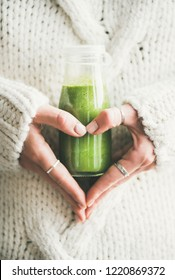 Winter seasonal smoothie drink detox. Female in knitted sweater holding bottle of green smoothie or juice making heart shape with her hands. Clean eating, weight loss, healthy dieting food concept