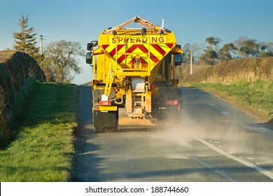 winter service vehicle or gritter spreading rock salt on the road surface to prevent icing in winter which causes accidents when vehicles slip on the highway.