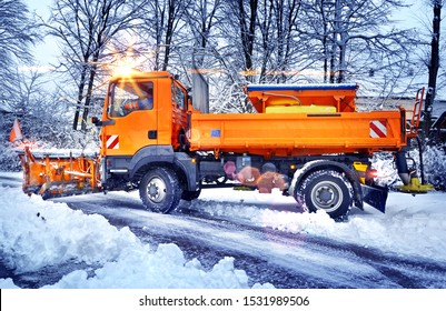 Winter service vehicle snow plow clearing side street in morning light