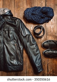 Winter set of men's warm clothing in casual style on the wooden background. new men's leather winter jacket, blue scarf, belt and shoes. Vertical photo
