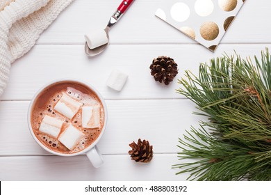 Winter sill life with hot cocoa, marshmallows, pine and cones, top view