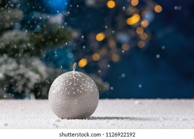 Winter silver round ball candle with snow and street lights in the background
