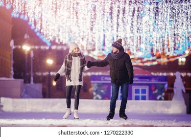 Winter skates, loving couple holding hands and rolling on rink. Illumination in background, night. Concept training.