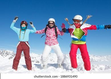 L'hiver, le ski et le plaisir. Trois jeunes enfants et adolescentes en vacances d'hiver dans les Alpes de Haute Savoie jouent et sautent dans la neige fraîche, sur les pistes de ski