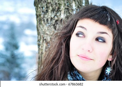 Winter smile. Happy girl in winter forest, smiling looking sideways