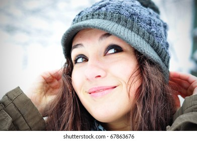 Winter smile. Happy girl in winter set-up, smiling looking upwards