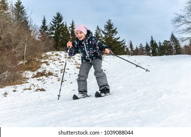 Winter snow activity. Front view of a girl skiing downhill surrounded by trees.