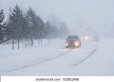 Winter, snow, Blizzard, poor visibility on the road. Car during a Blizzard on the road with the headlights.