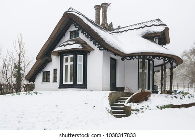 Winter snow covered thatched cottage in England