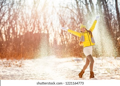 Winter snow fun woman playing throwing snow celebrating cold weather. Girl in yellow outerwear gloves, boots, hat, scarf, coat, enjoying outdoors in forest snowing in sun.