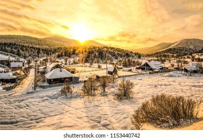 Winter snow mountain valley village sunset landscape. Russian sunset mountain village in winter snow panorama. Sunset winter snow mountain village in Russia