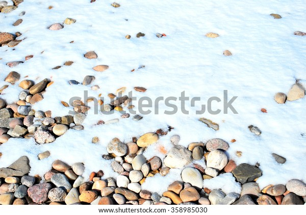 Winter snow over rocks displayed outdoors.